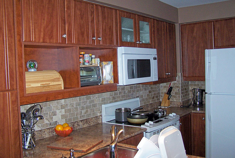 Wood kitchen with microwave and glass shelves