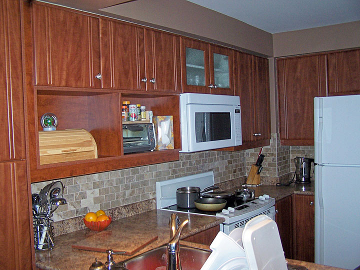 Larger Image - Simple and wise additions created a custom look with two open shelves that line up with the new microwave. The retro looking doors were manufactured in our factory completing the look the homeowners wanted.